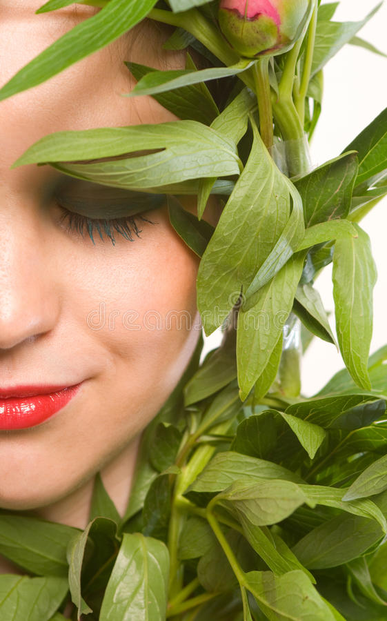 Naturaly beauty. Portrait of a young woman with green leaves of flowers aver face,eyes closed stock photography
