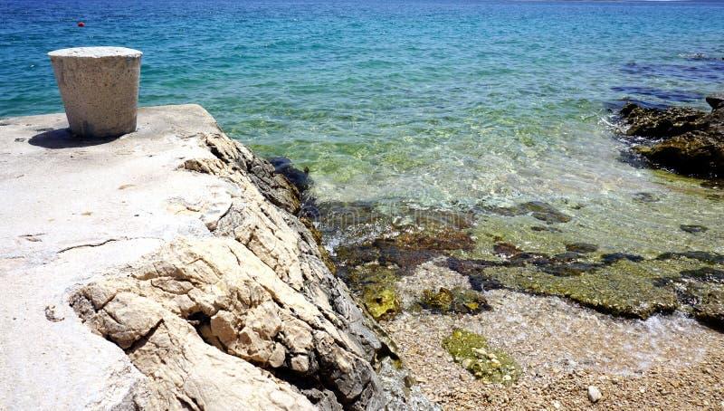 Naturbakgrund med detaljen av havskustlinjen och lösa Pebble Beach och sten som förtöjer pollaren royaltyfria bilder
