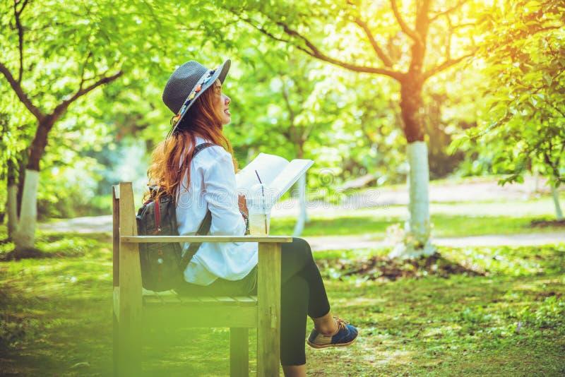 Nature asiatique de voyage de femme Le voyage d?tendent Lisez le livre sur le banc en parc en ?t? photos libres de droits
