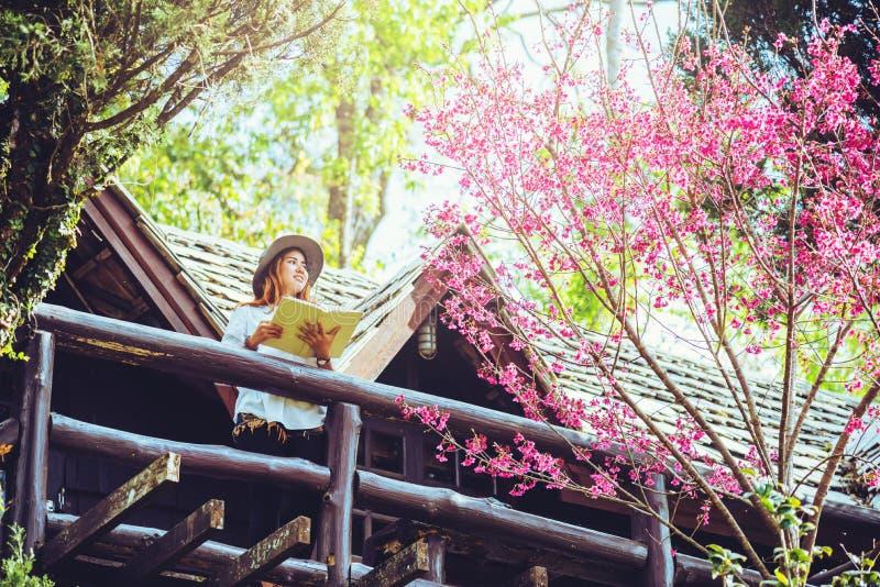 Nature asiatique de voyage de femme Le voyage d?tendent Livre de lecture debout le balcon de la maison images libres de droits