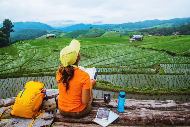 Nature asiatique de voyage de femme Le voyage d?tendent Livre de lecture debout le balcon de la maison En ?t? photo libre de droits