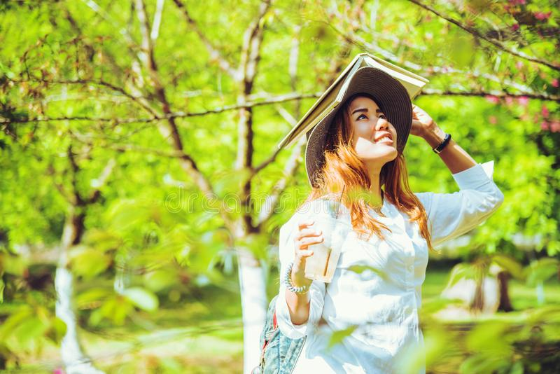 Nature asiatique de voyage de femme Le voyage d?tendent Livre de lecture sur en parc photos stock