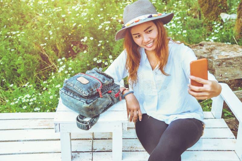 Nature asiatique de voyage de femme Le voyage d?tendent prise des photos Selfie sur le banc en parc en été photo libre de droits