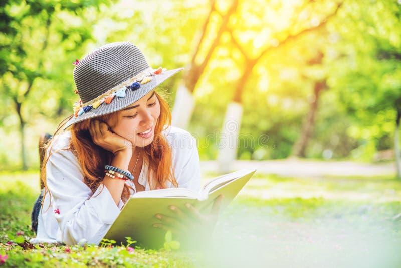 Nature asiatique de voyage de femme Le voyage d?tendent femme de sommeil lisant sur la pelouse en parc images stock