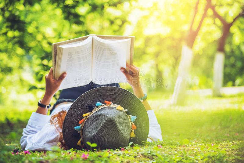 Nature asiatique de voyage de femme Le voyage d?tendent femme de sommeil lisant sur la pelouse en parc images libres de droits