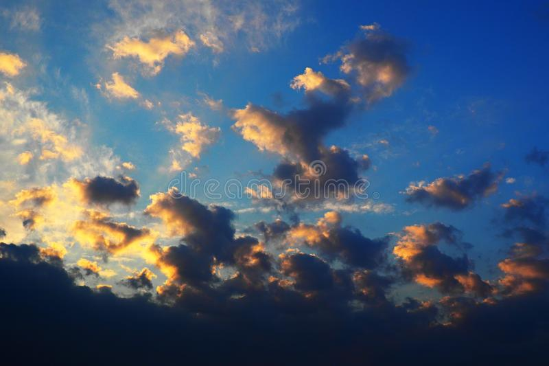 Gray and yellow clouds illuminated by rising sun. Nature background - blue sky with gray and yellow clouds illuminated by the rising sun royalty free stock images