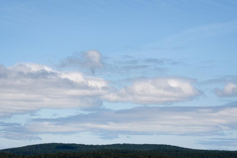 Nature background of blue sky and white puffy clouds, evergreen tree covered hill tops at the bottom, San Juan Islands stock photos