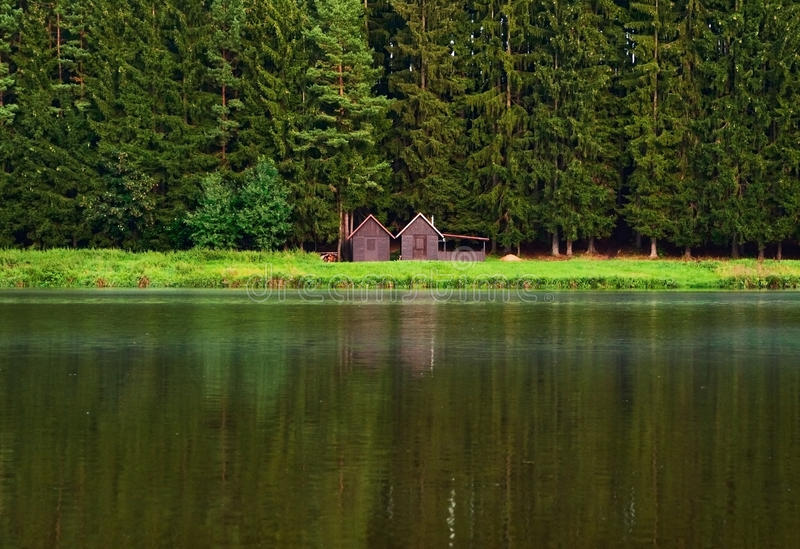 Nature background houses. Idyllic holiday or vacation place, cute houses by the forest and lake, nature background royalty free stock images