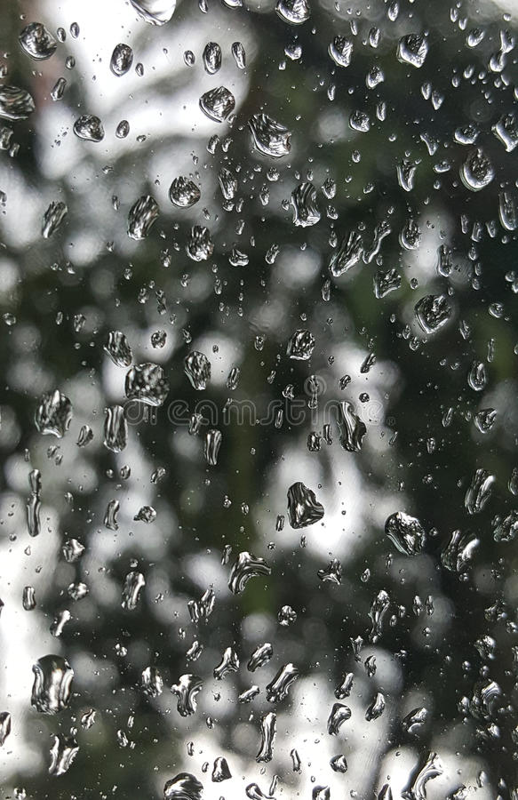 Nature background through rain drops on clear glass surface. Sad looking blurred nature background through rain drops on clear glass surface stock photos