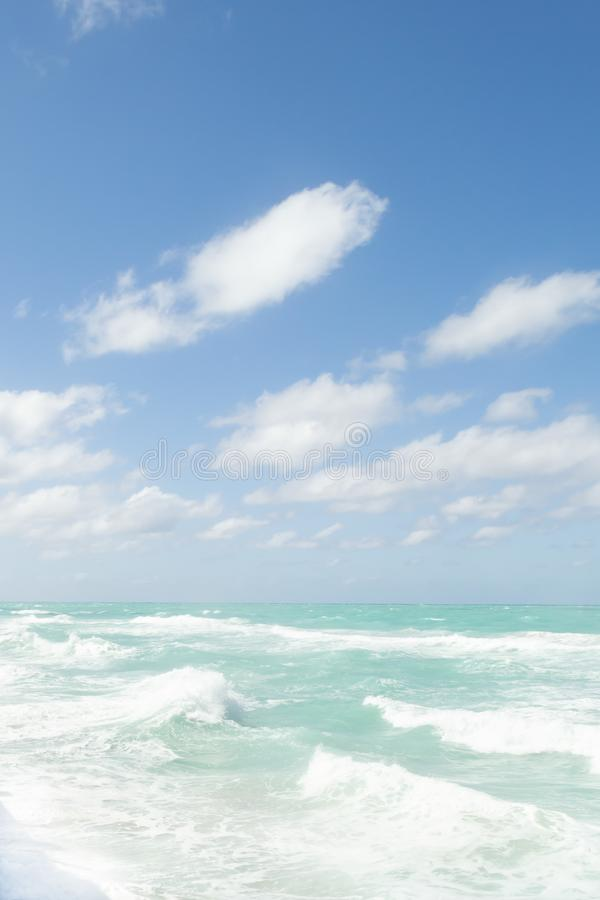 Nature background. Storm waves, blue water, fluffy clouds and sky. Vertical orientation stock photo