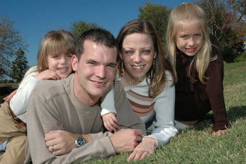 Nature family. An american family take their portraits in nature laying on the grassy ground. A family of four with two daughters and their parents stock photography