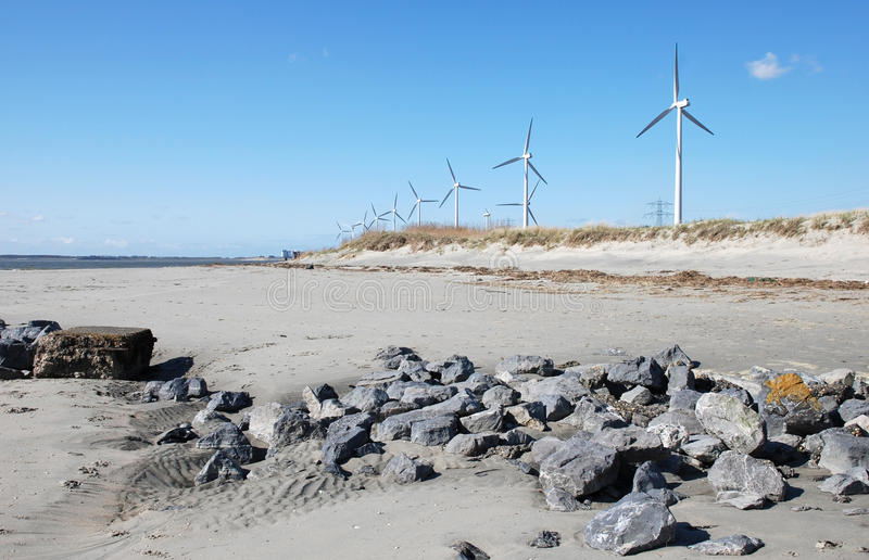 Nature green energy windmills. Rocks and windmills behind the dunes on a sunny dutch Kaloot beach royalty free stock photos