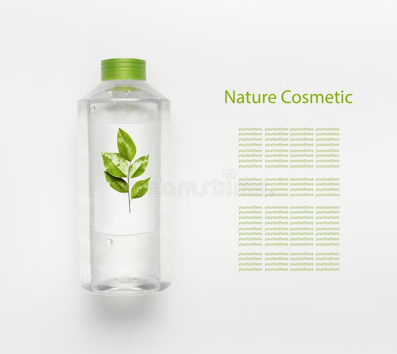 Nature herbal cosmetic concept. Transparent liquid bottle of toner, micellar water or cleansing product with green leaves. And branding mock up on white desk stock photography