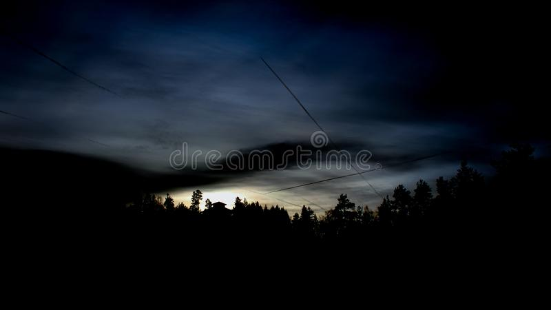 Late hour in the sky. Nature with a house in the silhouette blue hour dark sky in the light night stock image