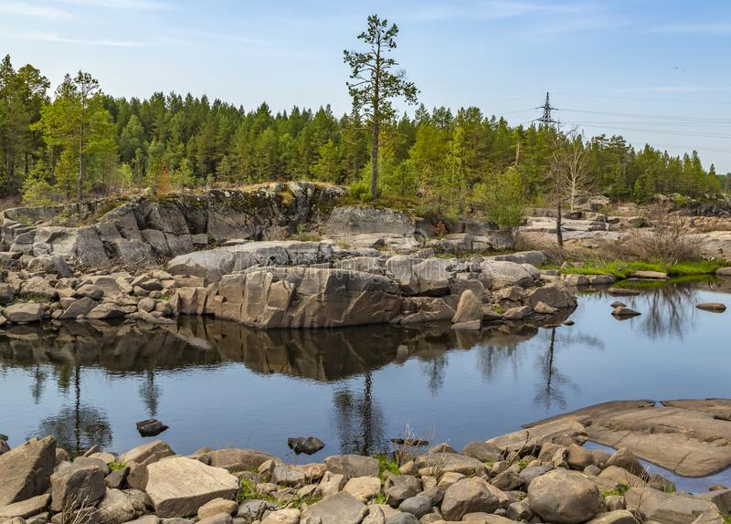 The nature of Karelia. Rocky shores are overgrown with trees and shrubs. Water in which the sky and numerous stones are reflected stock photos
