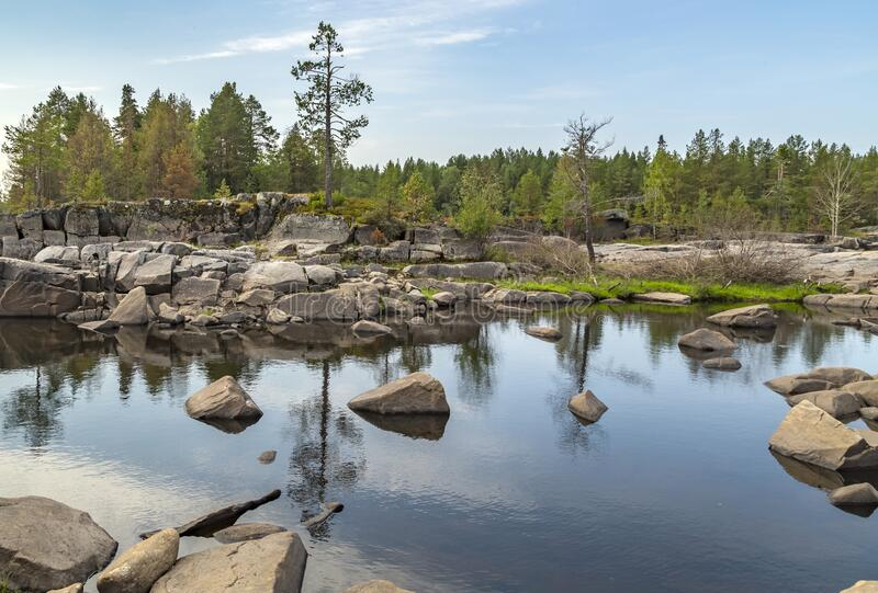 The nature of Karelia. Rocky shores are overgrown with trees and shrubs. Water in which the sky and numerous stones are reflected royalty free stock image