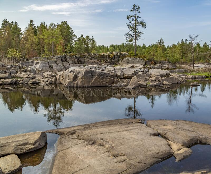 The nature of Karelia. Rocky shores are overgrown with trees and shrubs. Water in which the sky and numerous stones are reflected stock photo