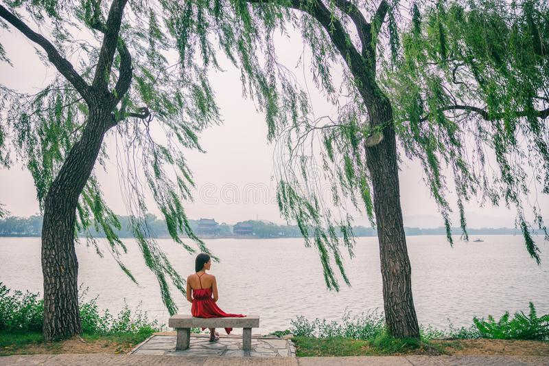 Nature lake woman sitting on park bench relaxing at view of Summer Palace in Beijing, China. Asia travel. Romantic scenery of lady. In red dress under weeping stock photo