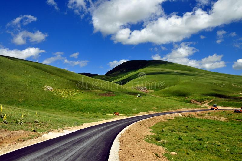 Nature landscape and new asphalt road. Beautiful background. New asphalt road landscape, Shar mountain Kosovo Industrial landscape with rollers that rolls a new stock photos