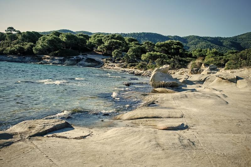 Nature landscape on sunny summer day. Nature concept. Rocky beach washed by waves, sea and green tropical forest on. Background. Rocky beach of sea, clear royalty free stock images
