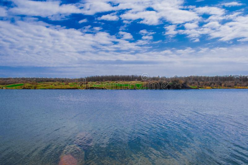 Nature, landscape, water on the ground in spring and summer. Bright saturated colors of the river, the lake. A blue bright sky wit. H clouds. The Grushevka River royalty free stock images