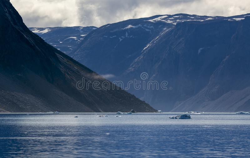 Ices and icebergs of polar regions of Earth. Nature and landscapes of Greenland. A travel on the scientific vessel. Studying of a phenomenon of global warming royalty free stock photography