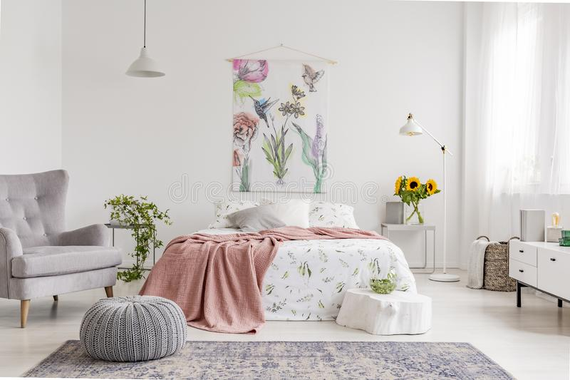 Nature lover`s bright bedroom interior with a wall art of flowers and birds painted on a fabric above a bed which is dressed in g royalty free stock photo