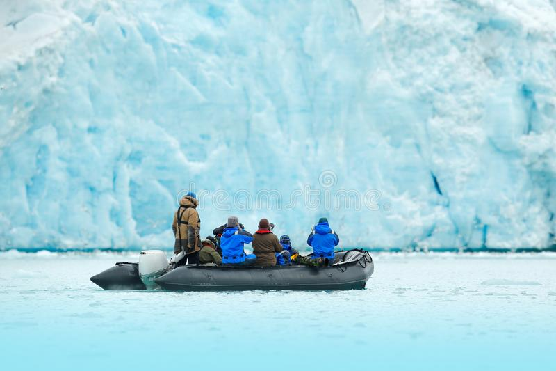 Nature lovers in Arctic Svalbard, Norway. Motor boat with tourists on the ice sea with glacier. Arctic cruise in winter, black pow royalty free stock image
