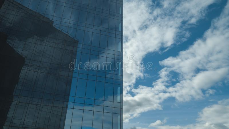 When nature meets high tech. Blue sky, reflected in a sleek wall of a high building royalty free stock photos