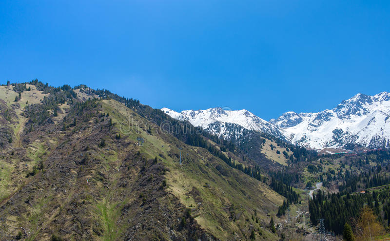 Nature of mountains, snow and blue sky, road on Medeo in Almaty, Kazakhstan, at summer stock photo