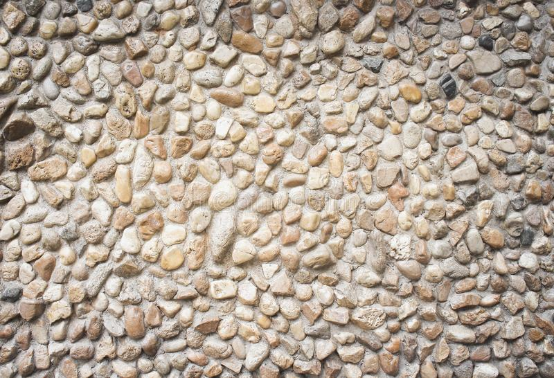 Nature patterns texture of multicolored stone decorative on concrete wall  for background royalty free stock images