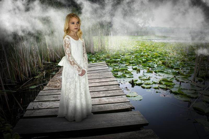 Nature, Peace, Love, Spirutual Rebirth. A young girl stands on a wooden pier by a lake with lily pads. The child is a metaphor for peace, hope, love, nature, and royalty free stock photography