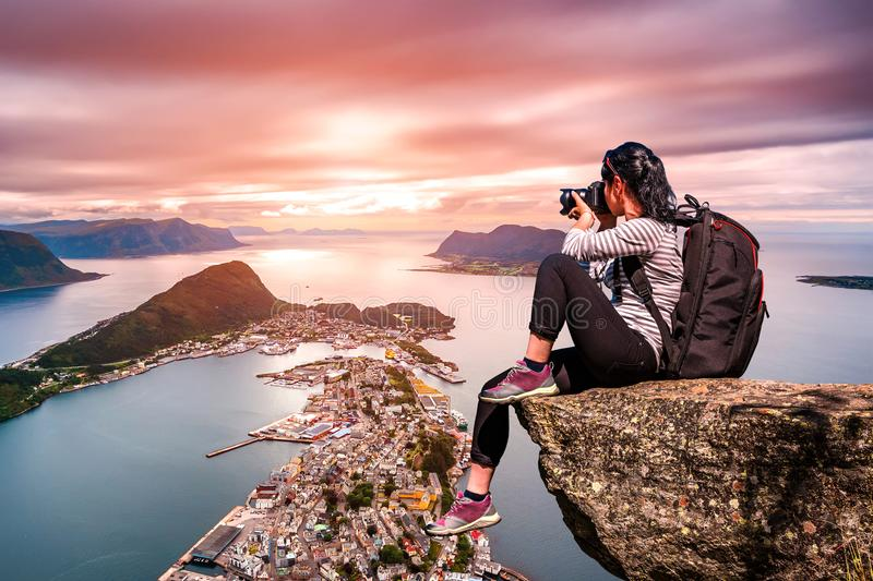 Nature photographer - Aksla at the city of Alesund , Norway. Nature photographer tourist with camera shoots while standing on top of the mountain. Aksla at the royalty free stock photos