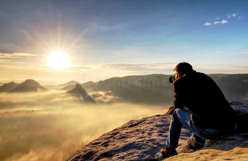 Nature photographer create art on view point in mountains. Man looking into viewfinder of his big camera, taking photo of borning stock photos