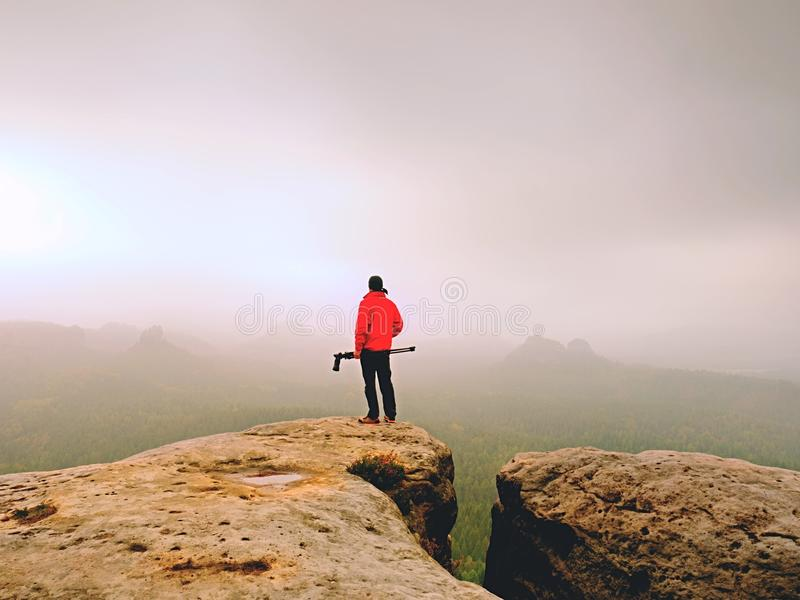 Nature photographer prepare camera to takes impressive photos of misty fall mountains. Tourist photographer. At sharp rocky edge on high view point, misty royalty free stock image