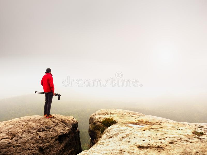 Nature photographer prepare camera to takes impressive photos of misty fall mountains. Tourist photographer. At sharp rocky edge on high view point, misty stock photo