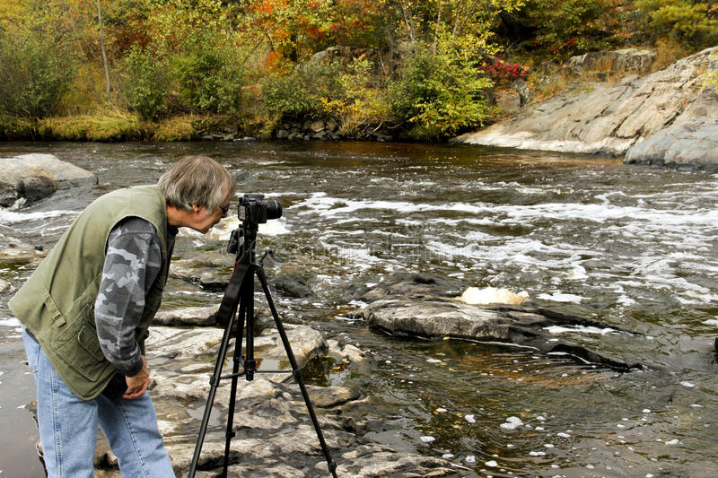 Nature Photographer. Taking photos of rushing river with an Autumn background stock photography