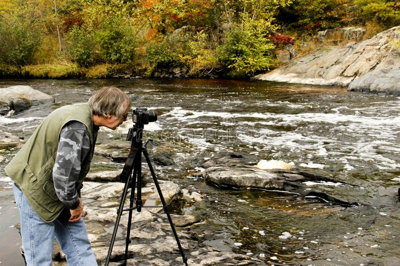 Nature Photographer in the wilderness. Nature Photographer taking photo`s in a wilderness river stock photo