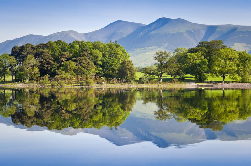 Nature reflected, English Lake District. Summer woodland reflected in a perfectly still Derwent Water with dramatic Latrigg mountain backdrop in the beautiful stock images