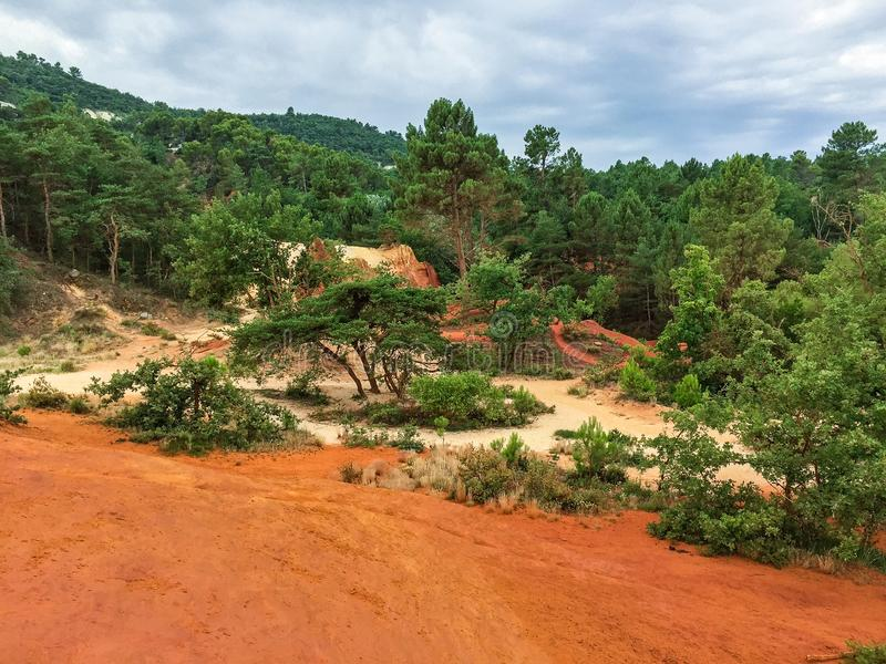 Nature reserve with red sand in France. Nature reserve called Colorado Provencal in France with trees and orange colored sand dunes high as mountaines a rainy royalty free stock photo