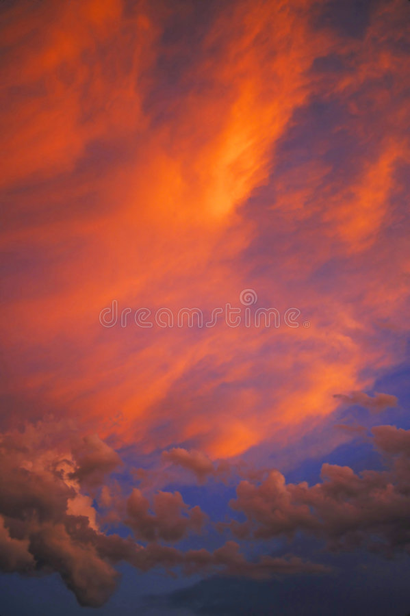 Nature's Surreal Beauty. Setting sun has given the cloud formation a temporary and fleeting brillant red coloring stock image