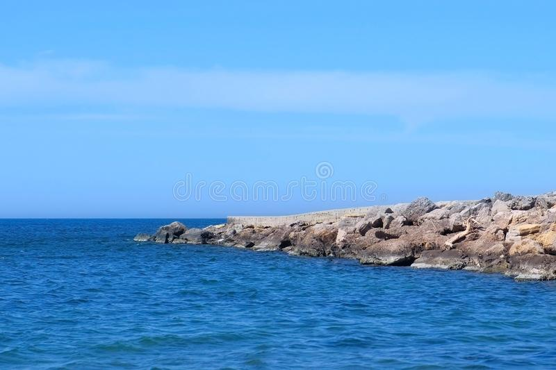 Nature seascape background with long stone pier stretching out to sea sunny day. royalty free stock photography