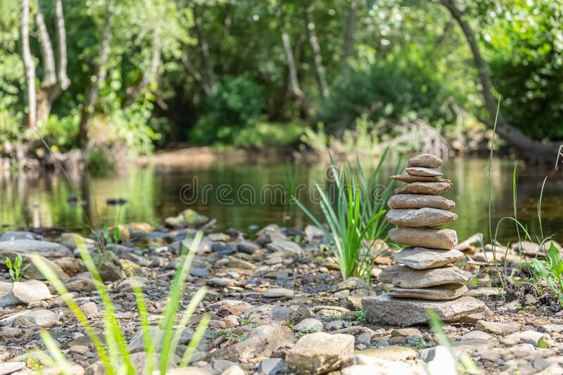 Nature Spa theme, pile of stones, calm river with trees, rocks and vegetation on the banks as background. Reflections in the water and bright colors stock photography