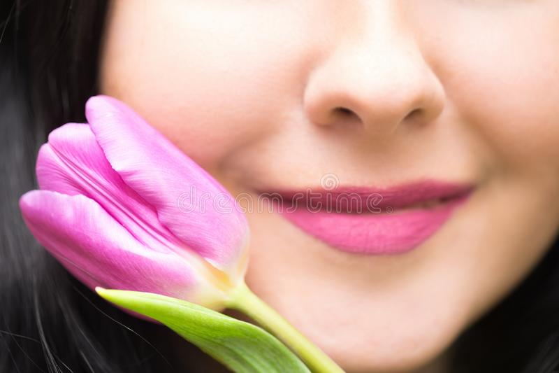 Nature or spring background. Young woman brunette with purple colored lips and purple tulip. Close up image with focus on the tuli stock images