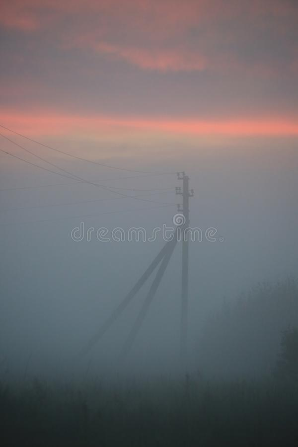 Nature and Technology. The support of the overhead power transmission line is seen in the fog on the background of a cloudy sunset. The time of the white nights royalty free stock image