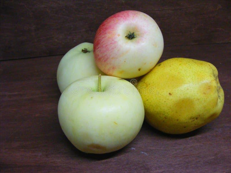 Naturemorte das maçãs e da pera na tabela de madeira marrom imagem de stock royalty free