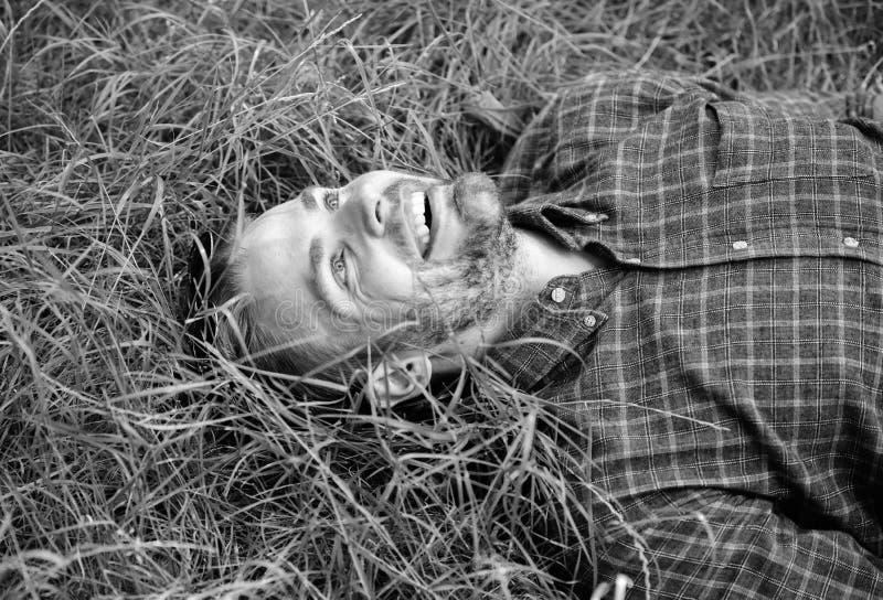 Naturen fyller honom med friskhet och inspiration Lägger den orakade grabben för mannen på äng för grönt gräs Fridsam grabb som ä arkivfoton