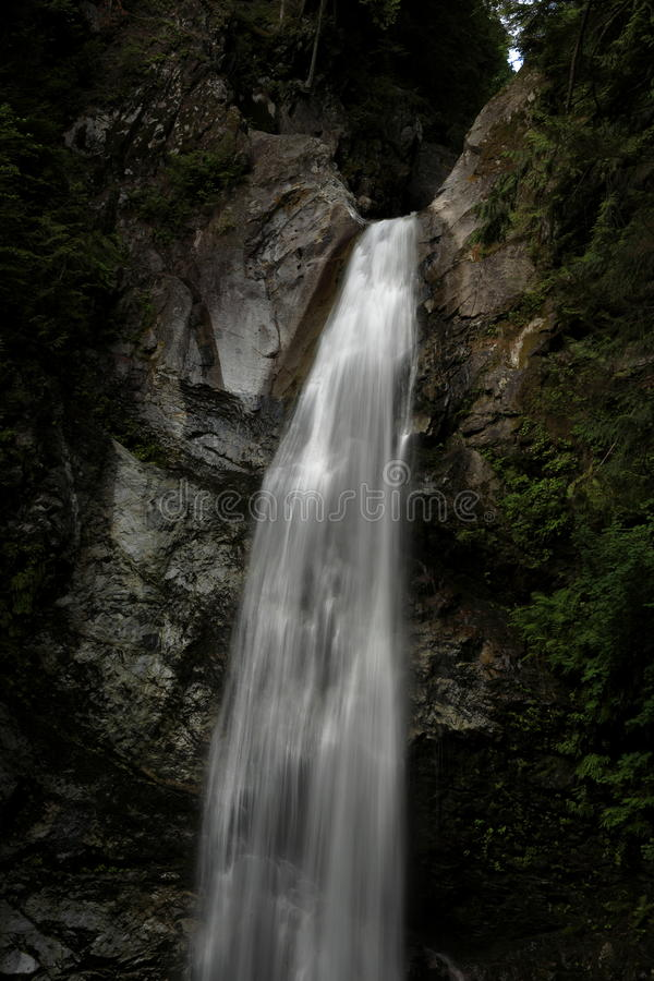 Waterfall flowing down a rocky cliff royalty free stock images