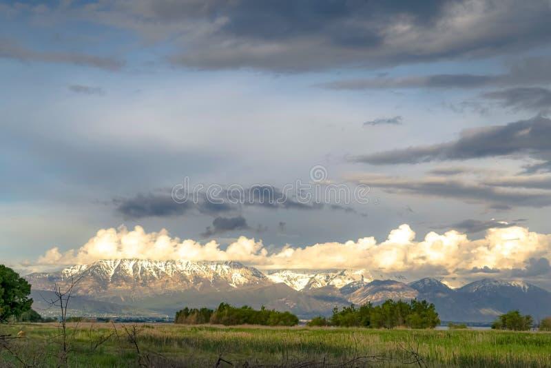 Natureza cênico com a montanha nevado ensolarado e o céu nebuloso sobre o lago e o vale imagens de stock royalty free