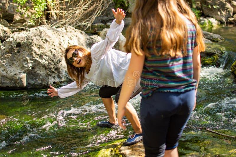Natureza de explora??o da mulher e da filha junto em um c?rrego ou em um rio foto de stock royalty free